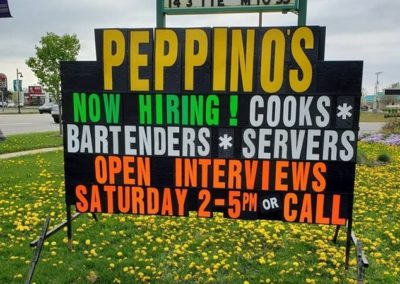 Peppino's Sports Bar in Jenison using a neon lettered black sign to find staff