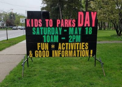 Garfield Park Neighborhood Association Kids to Park Day with a neon lettered black sign