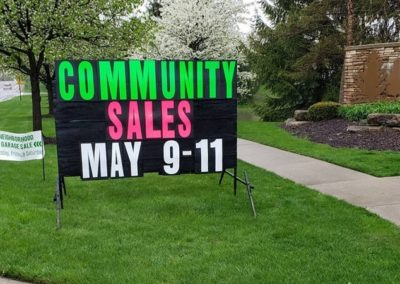 Community Garage Sales advertised with big black signs with neon letters