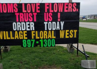 Village Floral in Lowell using a black sign promoting Mother's Day