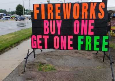 Those neon letters on a black sign sell fireworks